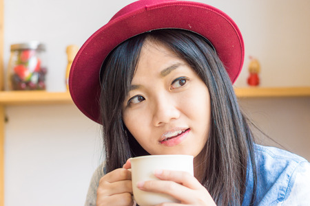 Beautiful asian woman drinking coffee in vintage cafe , Fashionable holding coffee photo