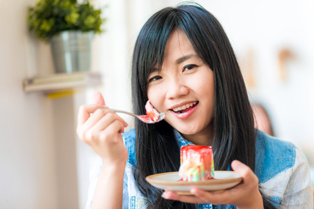 woman eating cake: Portrait of young asian pretty smiling woman eating cake at cafe, Lovely woman hold strawberry cake Stock Photo