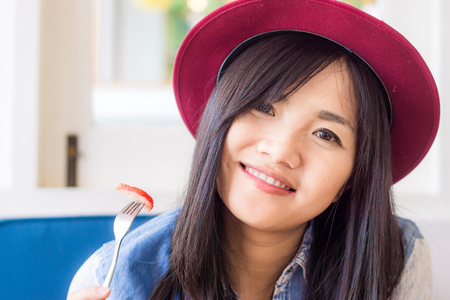 woman eating cake: Smiling young asian woman eating cake in bakery shop, Smiling and look so cute Stock Photo
