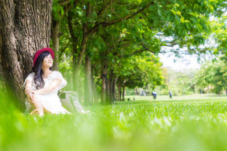 knapsack: Young fashion asian girl with knapsack in green park, Woman sitting in park