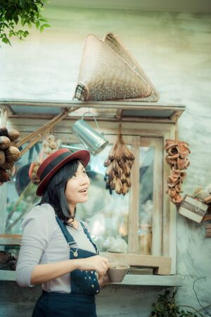 asian art: Asian beautiful cute girl in the cafe garden with coffee smiling, Vintage art tone