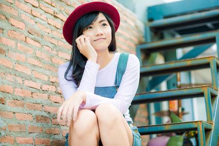 Junge asiatische hipster Frau sitzt und spricht am Telefon im Freien mit Baum Hintergrund und rotem Backstein