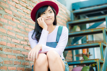 Young asian hipster woman sitting and talking on phone outdoor with tree background and red brick Stok Fotoğraf