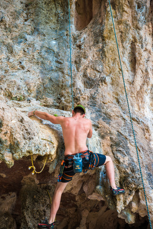 railay: RAILAY, THAILAND - JULY 20, 2015: Rock climbers on Railay beach, one of the most popular rock climbing locations in Asia.