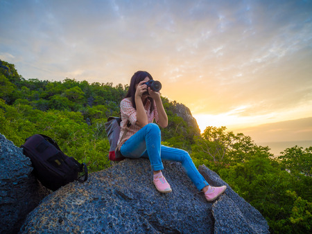 unrecognisable people: Young tourist with camera enjoying valley view from top of a mountain
