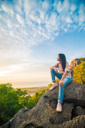 valley view: Asian hiker woman with backpack relaxing on top of a mountain and enjoying valley view during sunrise Stock Photo