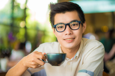 male portrait: Close up portrait of business asian man drinking coffee in vintage cafe, indoors.
