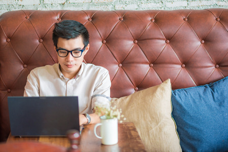 Young asian man drinking coffee in cafe and using laptop computer, Art coffe shop Standard-Bild