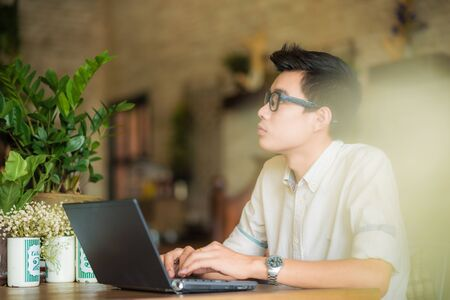 Young asian man drinking coffee in cafe and using laptop computer, Art coffe shop Stock Photo