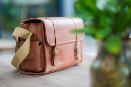 leather briefcase: vintage leather briefcase on wooden background Stock Photo