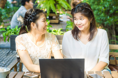businees: Asian businees women enjoying with her friend on laptop at coffee shop