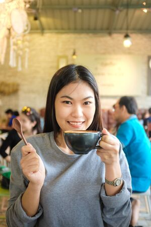 asian art: Beautiful cute asian girl in the art cafe  with coffee smiling, Women Coffee Shop Stock Photo