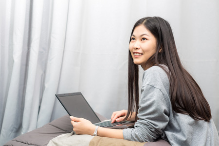 20 24 years: Portrait of attractive asian young lady sitting on bed uing laptop. Female working on laptop in bedroom.