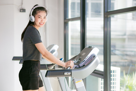 Asian woman exercising at the gym on a cross trainer, Woman training in a fitness club