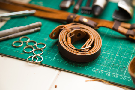 crafting: Leather crafting tools with camera strap, work table with old tools