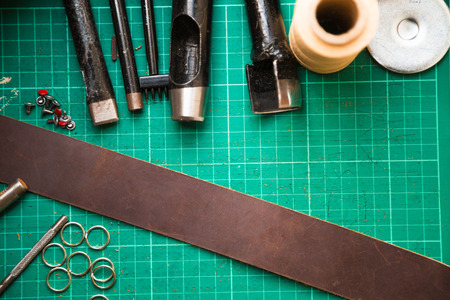 cuero vaca: Leather crafting tools on work table. Genuine cow leather