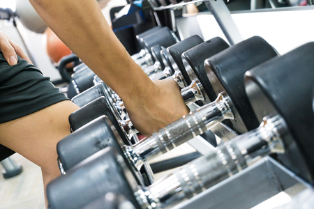 dumbell: Fitness Man Lifting Weights close up of arm iron dumbell Stock Photo
