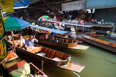 practiced: BANGKOK – MARCH 20: Wooden boats busy with people at Damnoen Saduak floating market on March 20, 2016 in Thailand. A traditional popular place of buying souvenir and selling still practiced in Damnoen Saduak  Thailand. Editorial