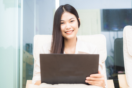 legs crossed at knee: smiling young beautiful woman using laptop computer by sitting at home