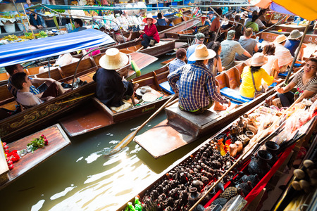 saduak: BANGKOK – MARCH 20: Wooden boats busy with people at Damnoen Saduak floating market on March 20, 2016 in Thailand. A traditional popular place of buying souvenir and selling still practiced in Damnoen Saduak  Thailand. Editorial