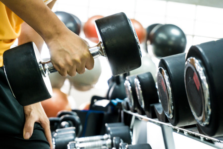 Arm of man lifting weights and exercising in fitness studio Stock Photo