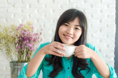 hot asian: Asian woman drinking coffee in the morning white art background Фото со стока