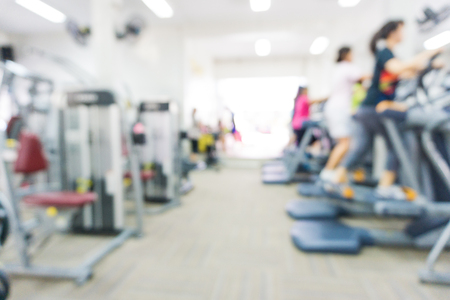 Blurred people running on treadmill at modern fitness centre
