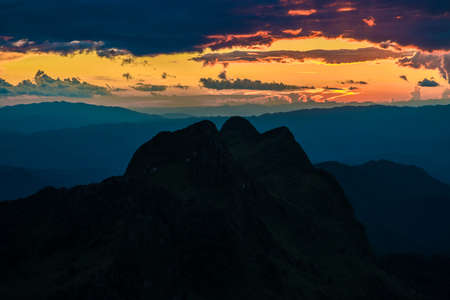 faintly visible: Silhouette sunset on the sub alpine mountain, Thailand Stock Photo