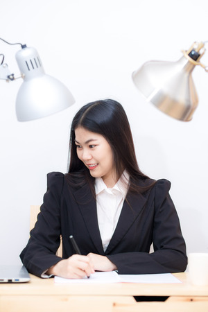 preoccupied: Portrait of business asian woman with laptop writes on a document at office white room Stock Photo