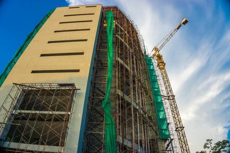 buildingsite: Concrete building construction with crane against blue sky Stock Photo