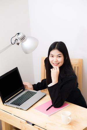 posting: Smiling asian businesswoman with laptop computer posting in white office looking at the camera