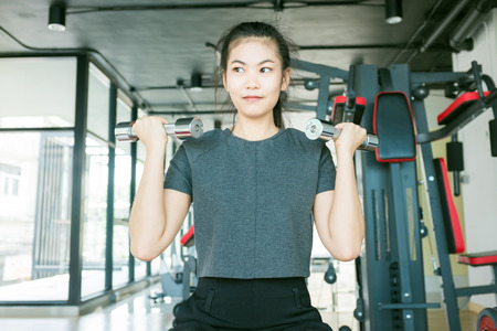 weightlifting gloves: Asian smiling strong woman weightlifting at the gym looking camera happy