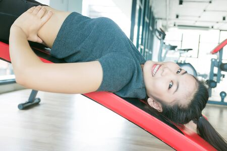 intervals: Beautiful athletic women working sit up intervals, working out in a gym
