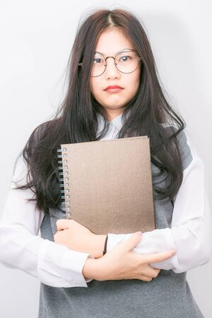 high spirited: Nerd beautiful young asian school girl hold lecture book on white background