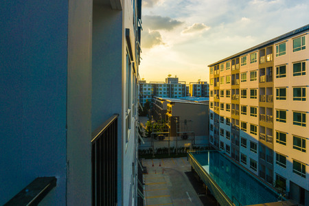 building feature: Condominium sunset with swimmingpool new block modern apartments, balconies and blue sky in the background