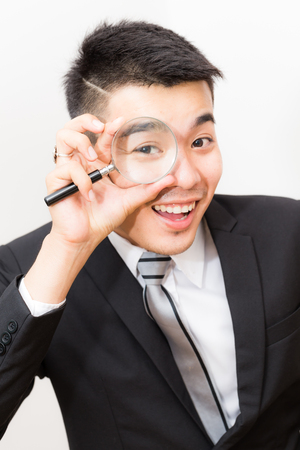 dinero falso: Business asian man Looking At camera Through Magnifying Glass close up on white