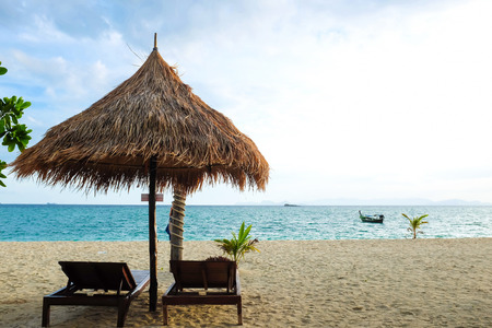 best place: Best place for recreation of sun umbrellas and wooden beds on tropical beach. Sea shore vacation