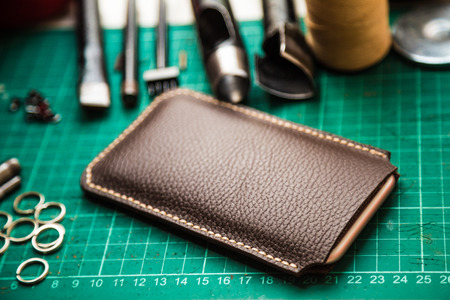 Genuine leather crafting tools make telephone case on green work table. Stock Photo