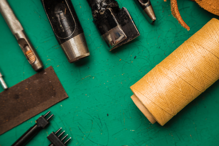 upholsterer: Top flat lay view of craftsman ship tool work space to skin leather products Stock Photo