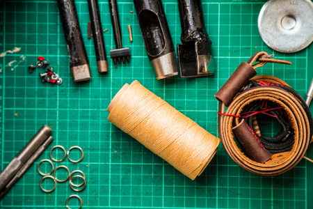 crafting: Leather crafting tools make camera strap still life on green work space board, Leather product
