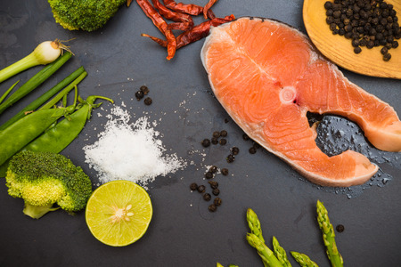 rosmarin: Raw Norway salmon fillet with fresh  spicy vegetable and olive oil on black background