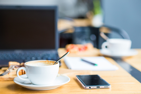 Laptop with cup of coffee and telephone on old wooden table in coffee shop blurred background