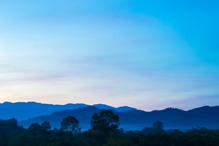 amanecer mañana brumosa del área montañosa con rayo de luz y la niebla Foto de archivo