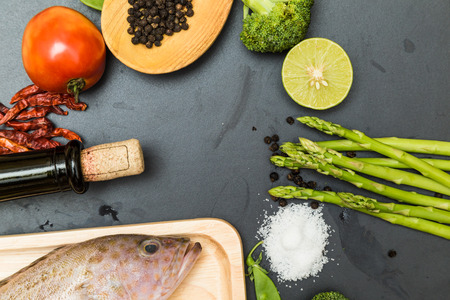 norvegicus: Raw fish grouper on wooden cutting board with asian spicy herb and wine on black cutting board
