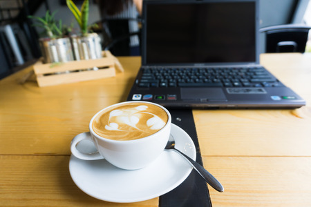 ultrabook: Latte art coffee cup and laptop for business on wooden table