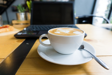 Latte art coffee cup and laptop for business on wooden table