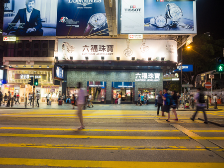 HONG KONG, CHINA - OCT 22: Crowded street view at night on October 22, 2015 in Hong Kong, China. With 7M population and land mass of 1104 sq km, it is one of the most dense areas in the world. Editorial