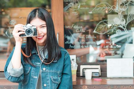 Retrato de la mujer asiática joven y bella inconformista con la cámara sin espejo en el café, el estilo de vida retro Foto de archivo