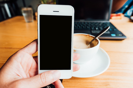 email lists: Businessman hand holding a phone with white screen against the background of the table in the office