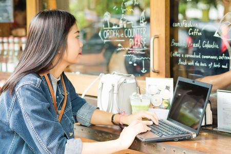 Mujer Indy inconformista usando la computadora portátil para el concepto de tecnología de las comunicaciones en las redes sociales tienda de café al aire libre Foto de archivo